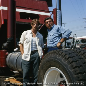 Claude Akins and Frank Converse pose behind a truck