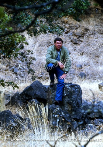 Claude Akins sits on a rock