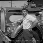 Claude Akins poses beside In Tandem Kenworth